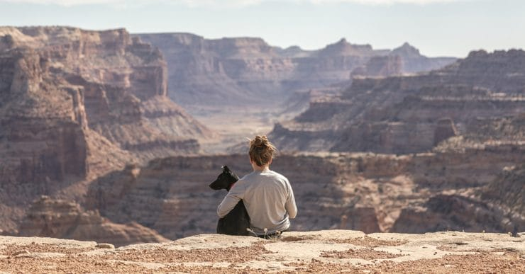 A woman and her dog sit at the side of a gorge