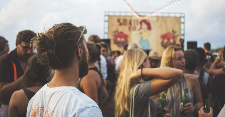 A crowd looks on in front of a stage at a festival.