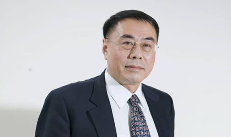 A photo of Hon Lik wearing a suit, standing against a white background
