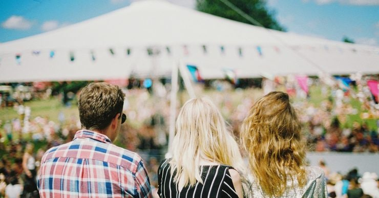 Three people sit on a verge watching music at a festival.