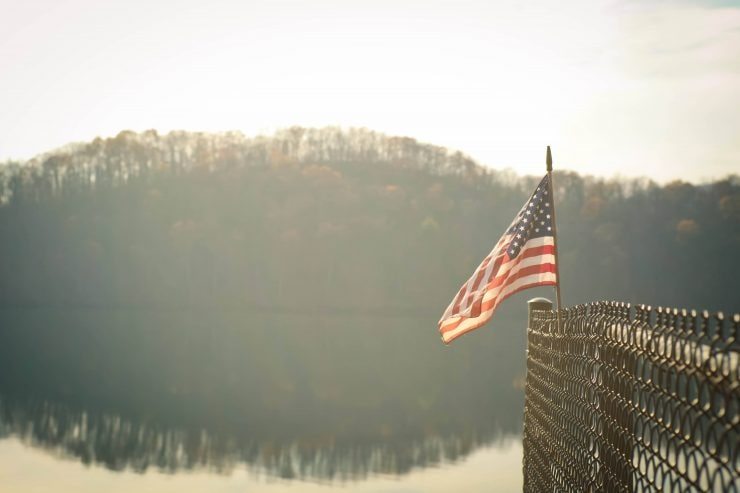 A small US flag leaning against a metal fence in front of a lake