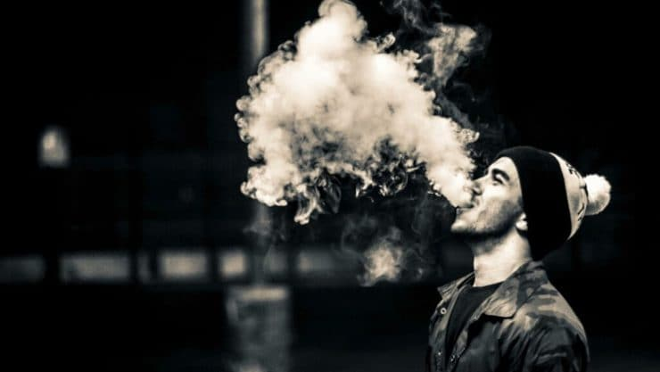 A black and white image of a man exhaling a cloud of vapor