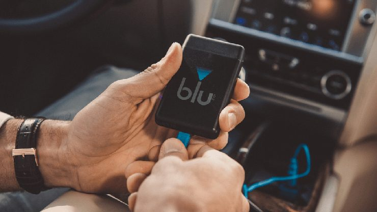 Inside a car, a man plugging in his blu PLUS Rechargeable Kit to charge using the blu Car Charger