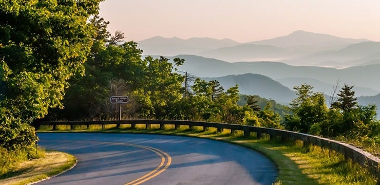A photo of Blue Ridge Parkway with rolling, misty hills in the background