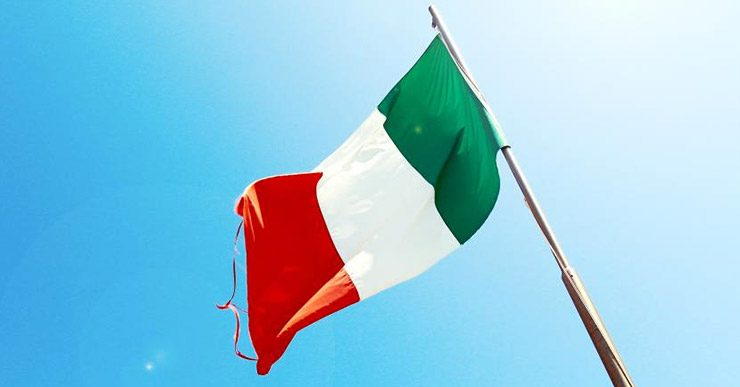 An Italian flag fluttering in the wind against a blue sky