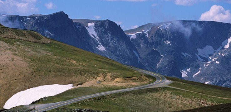 A shot of Beartooth Highway passing green fields and mountains