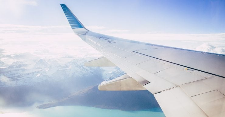 A photograph of a plane's wing as it flies over a range of coastal mountains