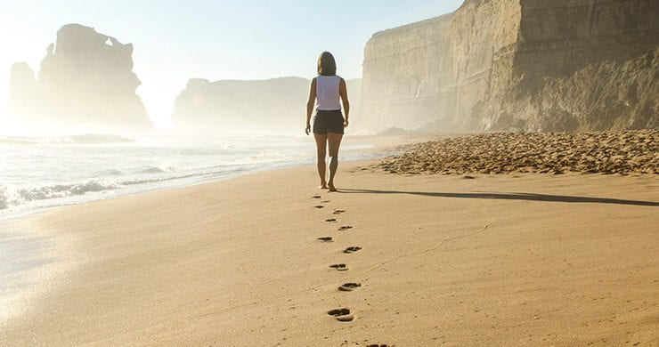 A woman walking on a beach leaving distinctive footprints in the sand