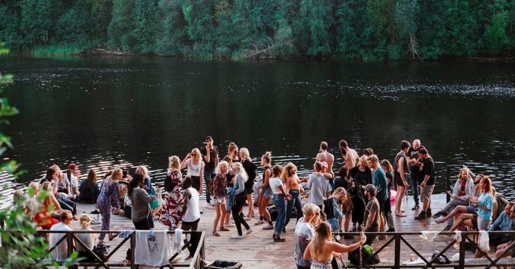 A crowd of people dancing next to a lake at a festival.