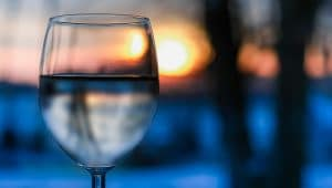 A glass of water on a table in front of the setting sun