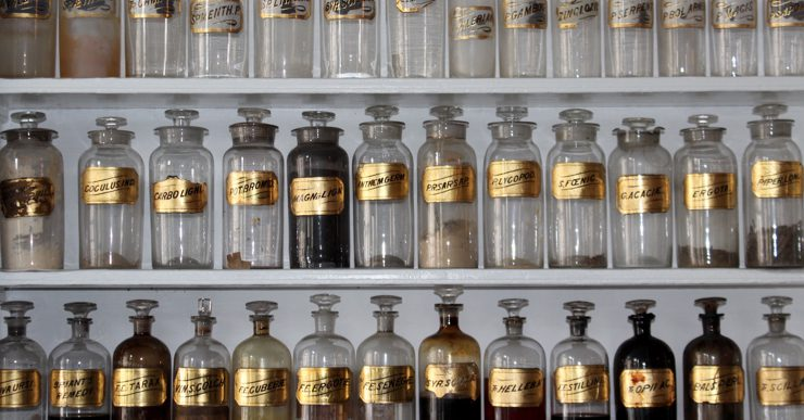 A shelf with many different ingredients in glass bottles