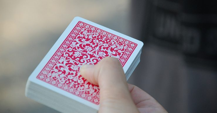 A hand holding a traditional deck of cards