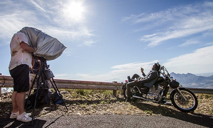 A cameraman shooting the motorbike from the blu advert set on a desert road under a clear blue sky